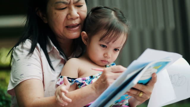thai mother is teaching her daughter to write and reading book at the terrace-education and lifestyles - control stock videos & royalty-free footage