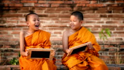 Thai novice sit on old wall and talk with friend