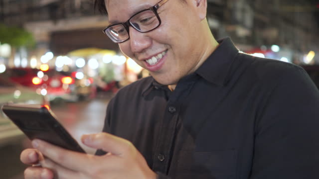 thai office man in eyeglasses using smartphone with street night bokeh background - one man only stock videos & royalty-free footage