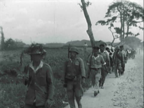 WS Thai or Filipino Army soldiers marching along dusty rural road as military lorry loaded with soldiers passes by / Korea