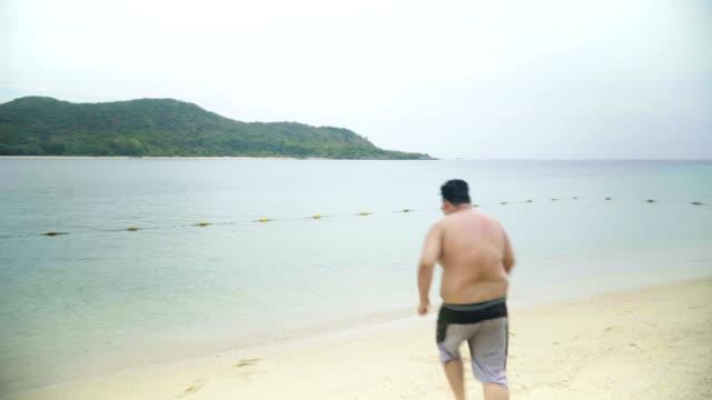 Thai übergewichtiger Mann laufen und springen ins Meer