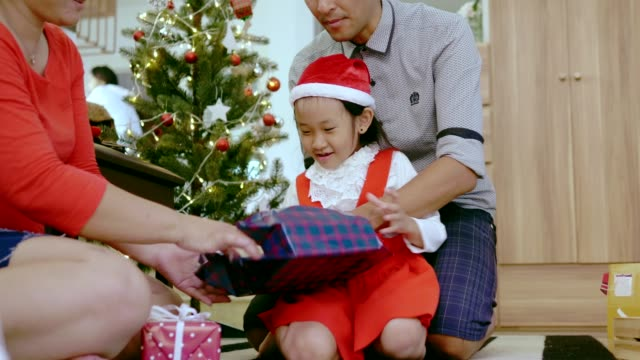 thai parent help her daughter to open christmas on december with positive emotion - unwrapping stock videos & royalty-free footage