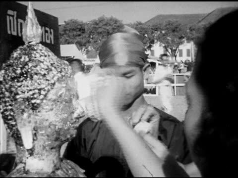 thai people placing gold leaf on statue of buddha donating donations vs statue of sitting buddha in pavilion in sanam luang vs thai people splashing... - acqua santa video stock e b–roll