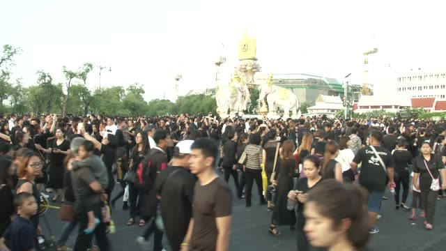 thai people walk near the grande palace after the motorcade carrying the body of king bhumibol adulyadej arrived to the grand palace in bangkok... - grande stock videos and b-roll footage