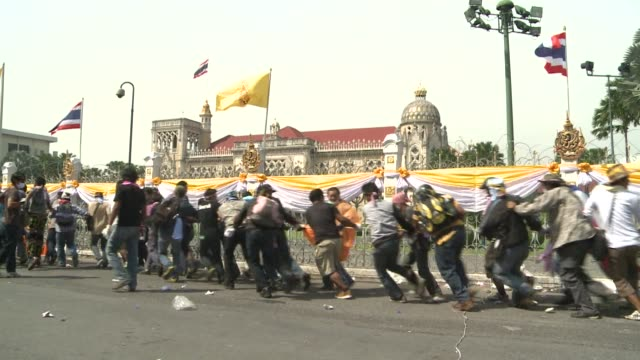 vídeos y material grabado en eventos de stock de thai police abandoned their defence of the besieged government headquarters on tuesday allowing unruly protesters to cross barricades in a dramatic... - aprobado
