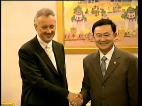 Thai Prime Minister investment in Liverpool ITN Bangkok Prime Minister Thaksin Shinawatra into room and greeting Liverpool FC Chief Executive Rick...