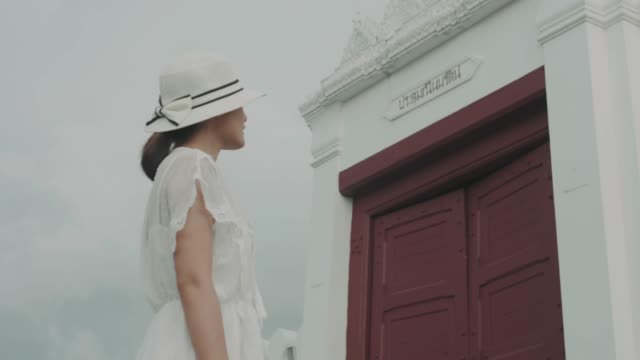 Thai retro beautiful woman is standing beside the door of Thai temple-travel on weekend in Bangkok