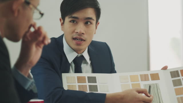 thai vertrieb architekten zeigt und präsentieren eine vielzahl von materiellen holzbrett für kunden - schneidebrett stock-videos und b-roll-filmmaterial