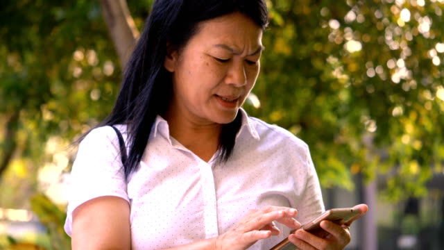 Thai senior adult is using smart phone while online chat to her friend at the garden