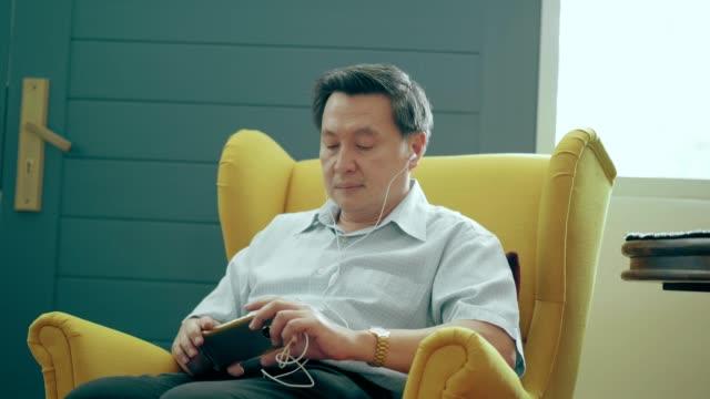 vidéos et rushes de les hommes aînés thaïlandais utilisant le téléphone pour écouter la musique et regarder le film au fauteuil - seniornaute