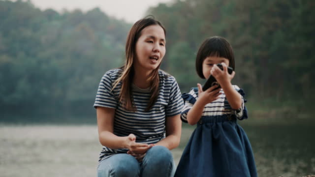 thai single mother with her daughter are using smartphone for talking to her father with positive emotion at the pond with green natural environment - natural condition stock videos and b-roll footage