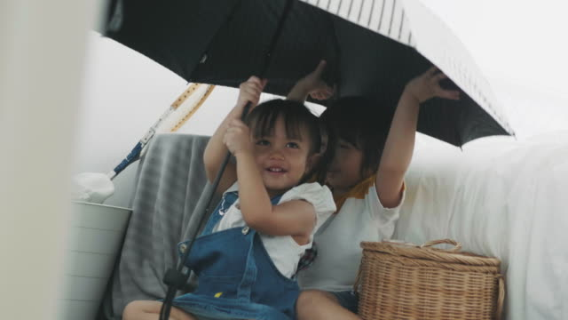 thai sister and brother is hiding while using umbrella for leisure activity - sharing stock videos & royalty-free footage