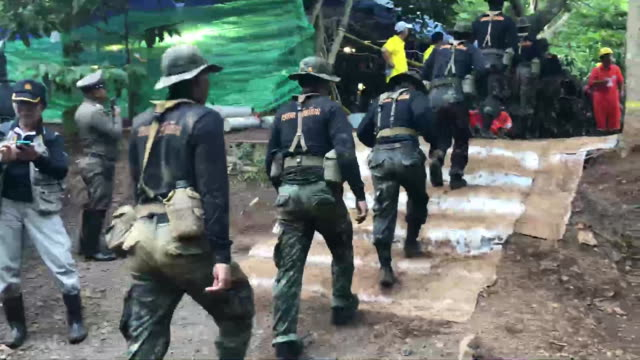 thai soldiers walking in line to the tham luang cave in thailand to assist with rescue operations on a soccer team and their coach who have been... - thailand stock videos & royalty-free footage