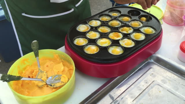 thai street vendor fries small quail eggs in the boiling pan - cooking crack in a spoon stock videos & royalty-free footage
