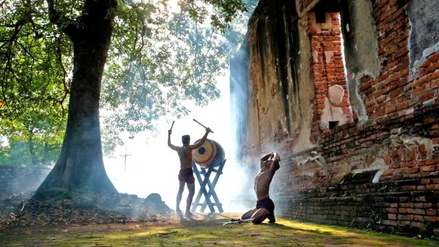 vídeos y material grabado en eventos de stock de espadachín tailandés baile show en el casco antiguo - histórico de la ciudad santo. guerrero sence de batalla de la guerra. bienvenido a concepto de tailandia. cultura de tailandia - gladiador
