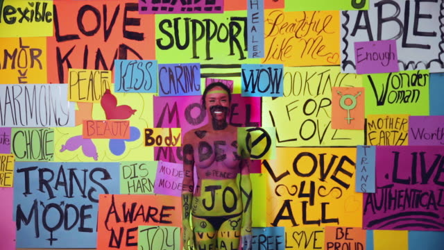 thai transgender woman blending into activism wall - aktivist stock-videos und b-roll-filmmaterial