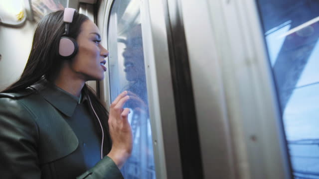 Thai transgender woman listening to headphones on subway train