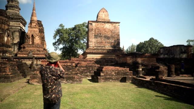 stockvideo's en b-roll-footage met thaise reiziger is het nemen van de foto in wat mahathat, sukhothai, thailand - menselijke rug