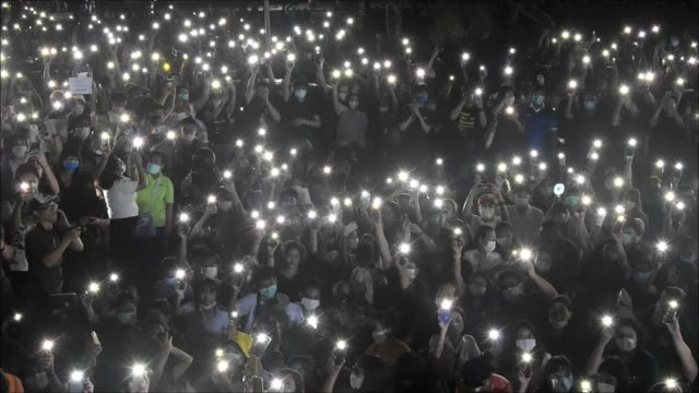 stockvideo's en b-roll-footage met thai university students and protesters turning on their smartphones' flashlights during a flash rally protest the government at kasetsart university... - zaklamp