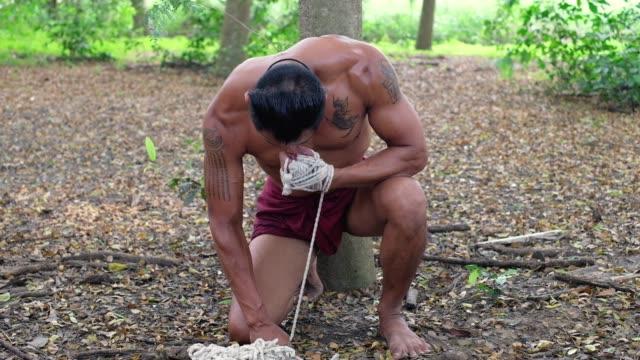 vídeos y material grabado en eventos de stock de guerrero tailandés en estado de ánimo enojado se prepara para la batalla. luchador de muay thai (boxeo tailandés) calle prepárate en el campo de batalla - histórico de la ciudad. bienvenido a concepto de tailandia. cultura de tailandia - gladiador