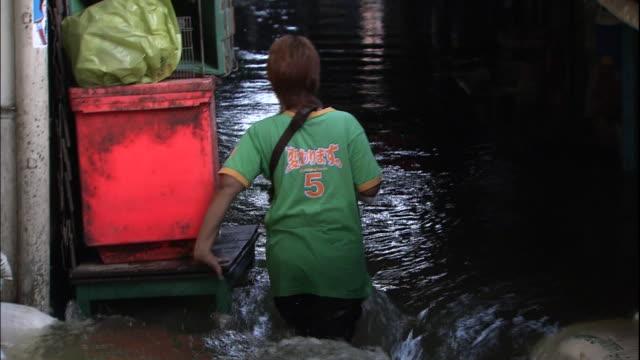 A Thai woman cautiously wades through hiphigh water