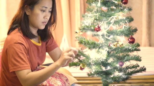 vídeos de stock, filmes e b-roll de mulher tailandesa decorando a árvore de natal em casa - loneliness