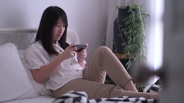 Thai woman is playing game on smart phone at her bedroom