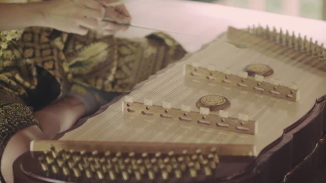Thailändische Frau spielt thailändisches Hackbrett-Musikinstrument