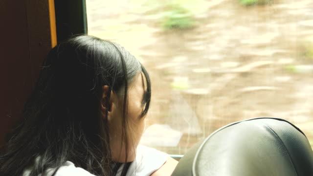 stockvideo's en b-roll-footage met thaise vrouw toeristische zit en zie de natuurlijke achtergrond terwijl express het gevoel treurig en eenzaam - forensentrein