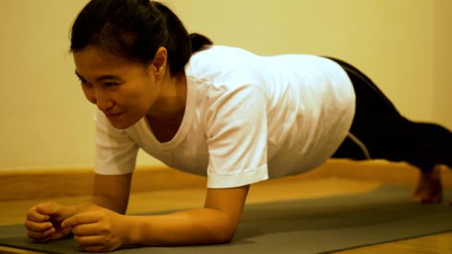 vidéos et rushes de femme thaïlandaise avec planches de bout droit pour sport préparation à sa chambre après le travail - planche de bois