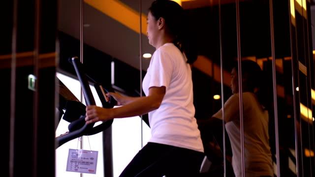 朝在庫ビデオ静止バイクに鍛えるとタイの女性 - インドアサイクリング点の映像素材/bロール