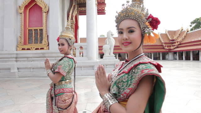 Thai women perform a traditional dance at a temple in Bangkok, Thailand.