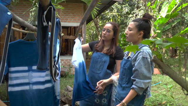 thai women tie batik dyeing indigo color hanging process dry clothes in the sun - dye stock videos & royalty-free footage