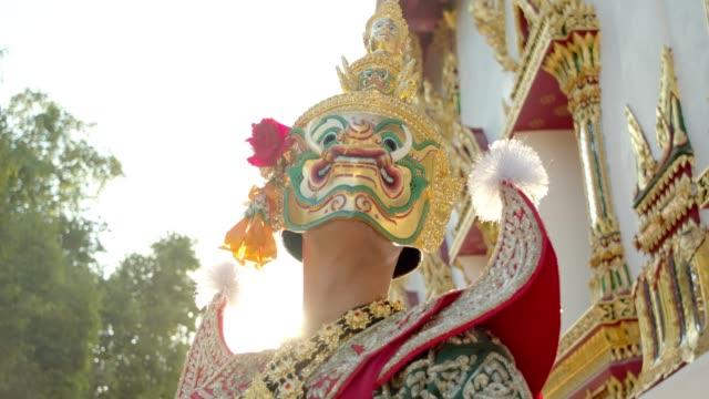アユタヤ県の美しい寺院で巨大なフェイスマスクを持つkhon.danceと呼ばれるマスクの下でタイの古代伝統舞踊。4kスローモーション - アユタヤ県点の映像素材/bロール