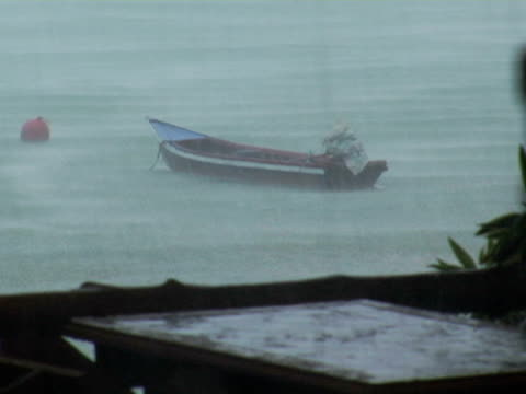 ms, thailand, ko phi phi, small anchored boat in heavy downpour rain and wind - anchored stock videos & royalty-free footage