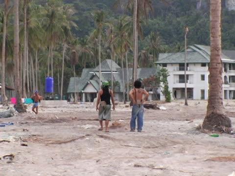 MS, ZO, Thailand, Ko Phi Phi, Two men walking on battered main road after tsunami, rear view