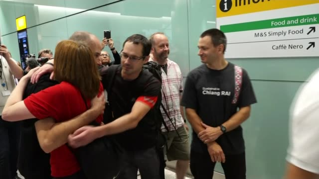 seven british divers return home england london heathrow int group of british cave divers along at airport terminal and hugging woman - itv放送点の映像素材/bロール