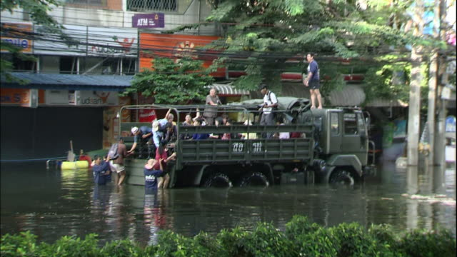 Thailanders crowd an army truck to escape Bangkok floods
