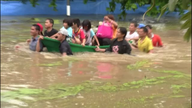 Thailanders push a small boat overloaded with evacuated children through a flooded street