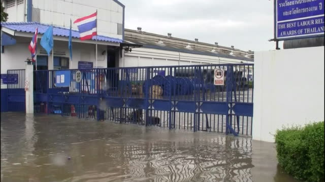 Thailanders stand in shallow flood water near stacks of sandbags