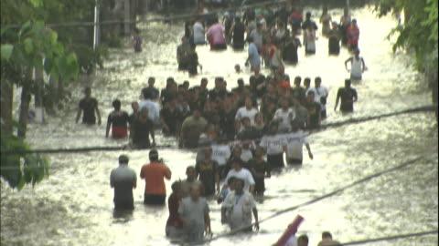 thailanders wade waist-deep through a flooded street. - walking in water stock videos & royalty-free footage
