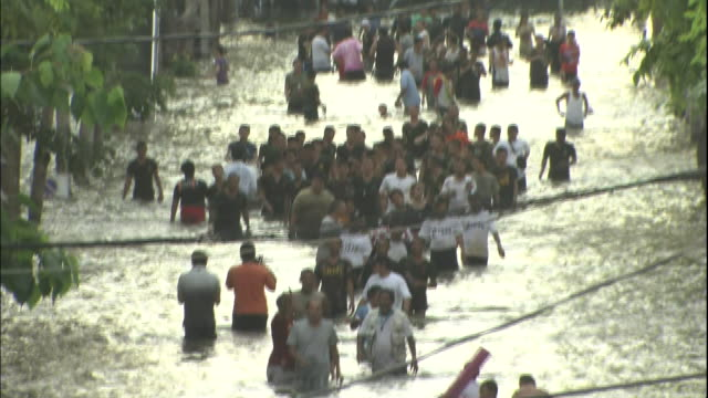 thailanders wade waistdeep through a flooded street - camminare nell'acqua video stock e b–roll