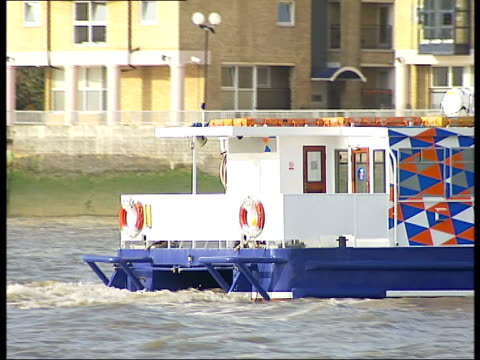 Thames clipper ferries operating Old style Thames clipper pulling away from dock and along through water/ General views Twin star commuter ferry...