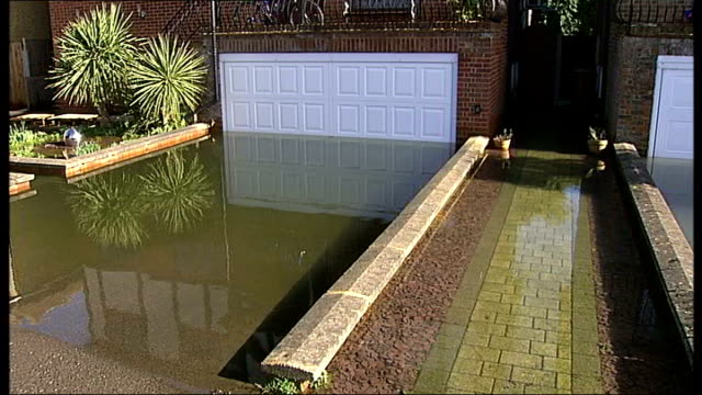 thames valley river levels look set to rise again england surrey ext clouds in sky tilt down swollen fast flowing river water pumping from hose into... - surrey england stock videos & royalty-free footage