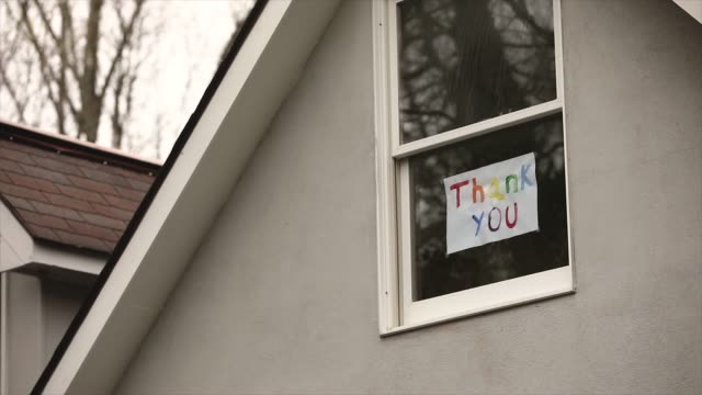 vidéos et rushes de thank you sign in window of suburban home - panneau