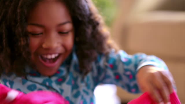 Thankful young girl opens Christmas present, admires her new pink sweater, and hugs her father