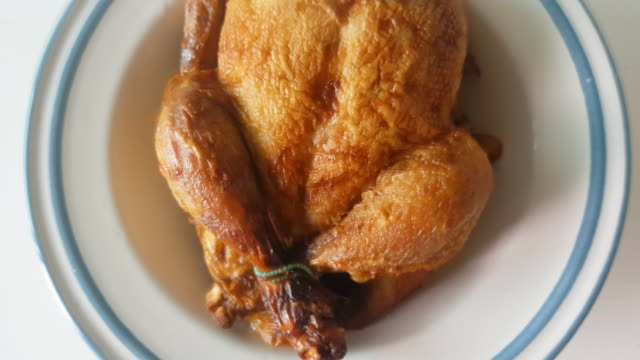 thanksgiving day dinner table setting with whole roasted turkey or chicken on plate with cutlery - thanksgiving plate stock videos & royalty-free footage