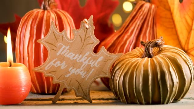 vidéos et rushes de décoration de thanksgiving avec des citrouilles et la carte de voeux sur le fond illuminé et une table en bois rustique - décoration de fête
