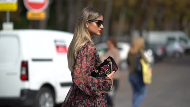 Thassia Naves wears a floral print lace dress red leather boots sunglasses a bag outside Issey Miyake during Paris Fashion Week Womenswear...