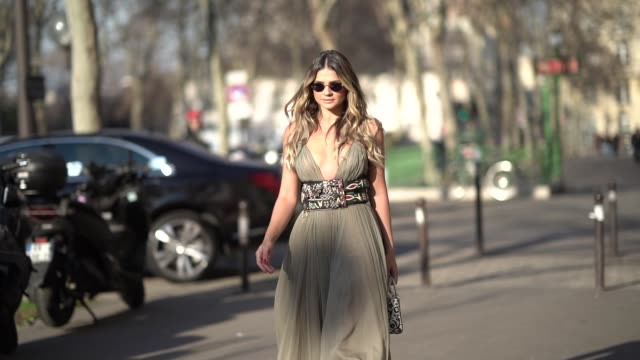 Thassia Naves wears a green pleated dress a large belt with colored embroidery a Dior bag sunglasses outside Dior during Paris Fashion Week Haute...